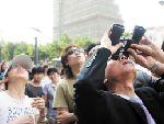 围观市民用望远镜观察女子的情况。