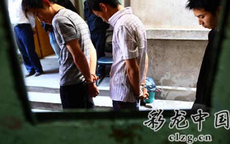 昨日,3个入室抢劫的犯罪嫌疑人被押解到塘双路指认现场。记者 赵伟
