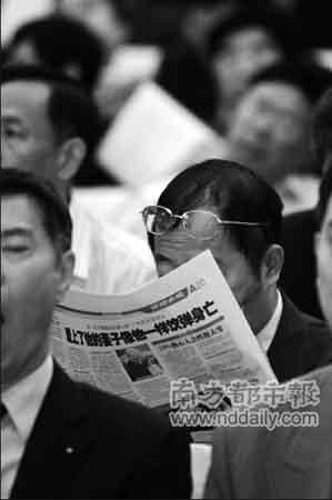 在市政协会议开幕式上,一名委员在认真地看报纸。