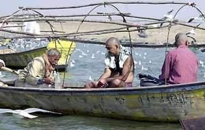 一名印度牧师(左)在安拉阿巴德的森格姆(恒河、亚穆纳河和萨拉索沃蒂河的交汇处)为一名准备将亲人的骨灰撒入河水中的男子(右)做宗教仪式。