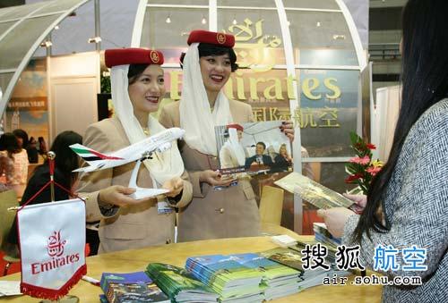 """身着米色制服、头带鲜艳的红色礼帽和迷人的白色沙巾,两名阿联酋航空公司乘务员在今日开幕的""""中国出境旅游交易会""""上亲切和蔼地展示阿航机上服务。阿航为业内观众带来了新近在北京市场推出、装备了头等舱私人包间的空客A340-500型飞机。"""
