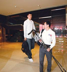 姚明的经纪人陆浩为他拿着拐杖