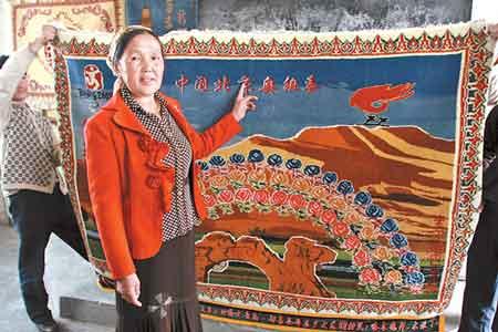 """挂毯""""飘逸楼兰迎奥运""""由该村8名维吾尔族妇女织就,长1.8米,宽1.2米,左上角织着北京奥运会会徽,右上角是奥运火炬接力标志图案,中间的主背景是代表鄯善县特色的库木塔格沙漠、泉水、绿洲和驼队,中央是象征56个民族大团结的56朵牡丹花。图为哈木热汗·木依丁(左二)向记者介绍挂毯""""飘逸楼兰迎奥运""""。(本报记者周磊摄)"""