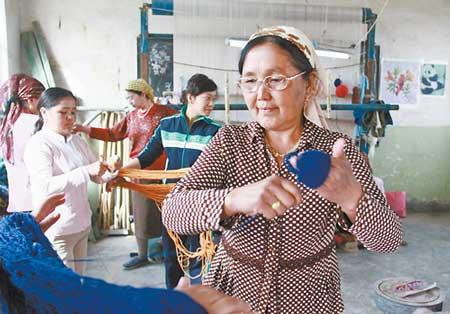 哈木热汗·木依丁说,开好奥运会是56个民族共同的心愿,她想用挂毯表达对奥运会的祝福。图为4月6日,哈木热汗·木依丁准备制作新的挂毯。(本报记者周磊摄)