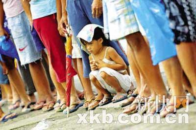 ■为了解决国民的日常口粮问题,菲律宾政府近日从越南购入大批大米,以低价卖给本国居民。图为一个小姑娘在妈妈的带领下,顶着烈日排队买米。