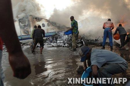 4月15日,在刚果(金)东部的戈马市机场附近,当地人围在失事客机旁救火。当天下午,刚果(金)私营航空公司埃瓦-博拉公司的一架客机在这里坠毁,机上乘客和机组人员近百人,目前救援人员仅发现了数名幸存者。 新华社/法新