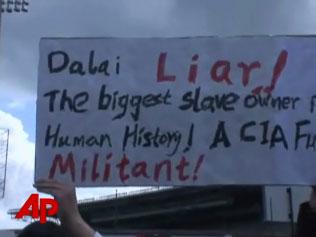 人们举起标语,抗议达赖(西雅图电视台视频截图)
