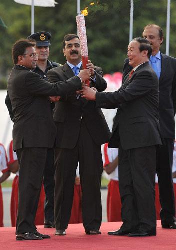4月16日,在巴基斯坦体育中心,北京奥运会火炬接力运行团队总指挥、北京奥组委执行副主席蒋效愚(前右)将火炬交给巴基斯坦总统穆沙拉夫(左)、总理吉拉尼(中)。新华社记者安治平摄