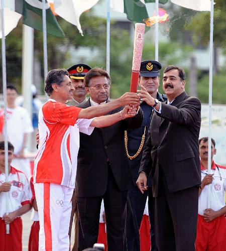 4月16日,在巴基斯坦体育中心,巴基斯坦总统穆沙拉夫(中)、总理吉拉尼(右)将火炬交给第一棒火炬手、1976年奥运会曲棍球铜牌获得者萨米乌拉·汗(左)。 新华社记者安治平摄