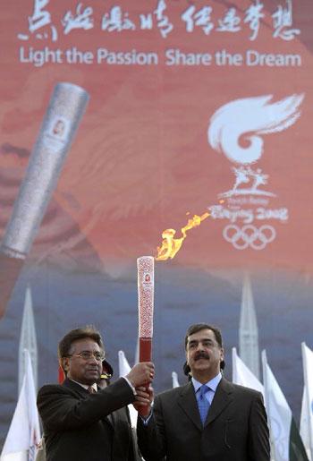4月16日,在巴基斯坦体育中心,巴基斯坦总统穆沙拉夫(左)和总理吉拉尼(右)共举火炬。当日,北京奥运会圣火传递活动在巴基斯坦伊斯兰堡举行。这是北京奥运会圣火境外传递的第十站。新华社记者吕小炜摄。
