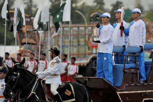 4月16日,在巴基斯坦体育中心,护火手手持火种灯和火炬乘马车出场。新华社记者吕小炜摄
