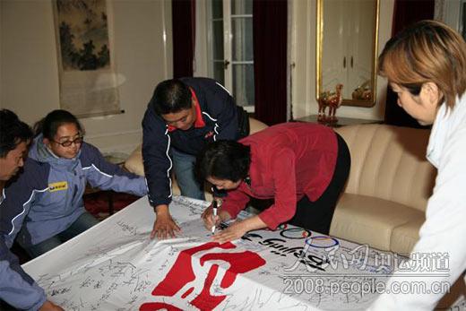 """使馆一等秘书王海娟为北京奥运会和""""龙行天下耀中华""""活动签名。"""