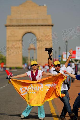 图文:两名华人观众兴奋的在印度门前翩翩起舞