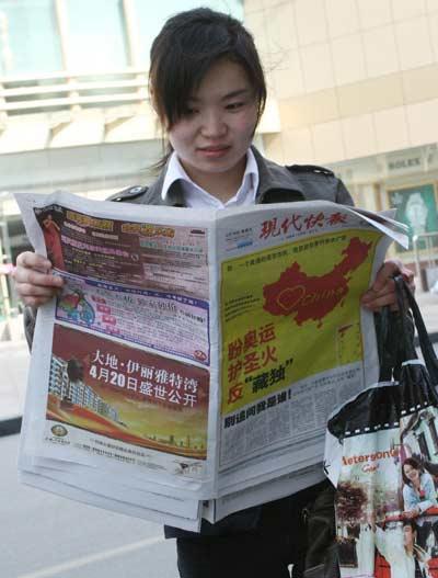 昨天,市民们被当日出版的现代快报所吸引。  快报记者 黄颢 摄
