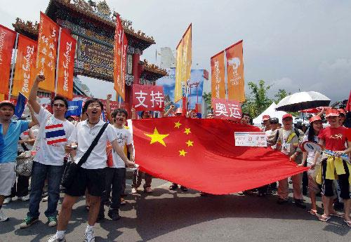 4月19日,当地华人华侨和中国留学生在圣火传递起点――曼谷唐人街耀华力路的中国门迎接圣火。当日,北京奥运会圣火传递活动在泰国首都曼谷举行。这是北京奥运会圣火境外传递的第十二站。 新华社记者公磊摄