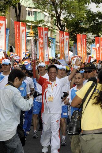 4月19日,第一棒火炬手、曼谷市常务副秘书长阿南·西里帕差腊蓬手持火炬传递。当日,北京奥运会圣火传递活动在泰国曼谷举行。这是北京奥运会圣火境外传递的第十二站。 新华社记者戚恒摄