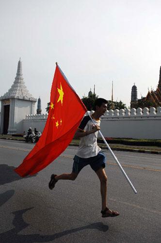 4月19日,一名青年追赶火炬传递队伍。当日,北京奥运会圣火传递活动在泰国曼谷举行。这是北京奥运会圣火境外传递的第十二站。 新华社记者凌朔摄