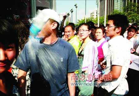 16日,昆明家乐福门口,反对抵制的朱先生被抗议者推搡,并遭矿泉水瓶袭击。云南信息报记者段玉良摄