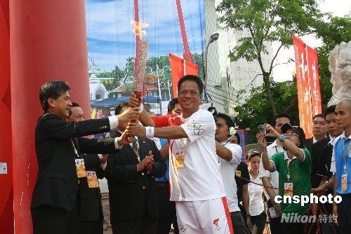 """4月19日下午3时15分,祖籍中国海南的泰国第二代华裔阿南·诗里帕差腊蓬从曼谷市市长阿皮拉手中接过""""祥云""""火炬,北京奥运圣火在此间的传递正式开始。图为阿南·诗里帕差腊蓬(右)从曼谷市市长阿皮拉手中接过""""祥云""""火炬。 中新社发 沈晨 摄"""