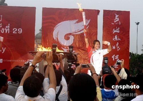 4月19日傍晚6时10分,雅典奥运会女子举重冠军芭薇娜·通戍在五世王铜像广场用手中的火炬点燃了圣火盆。图为芭薇娜·通戍点燃圣火盆后向民众致敬。 中新社发 沈晨 摄