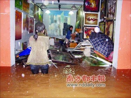 """前晚,深圳大芬村一画廊的员工打捞浸泡在水中的油画。当晚,""""浣熊""""来袭,仅仅10分钟,大芬村浸水一米余深,几乎所有画廊都被水浸,据称损失上亿元。胡荣燕摄"""
