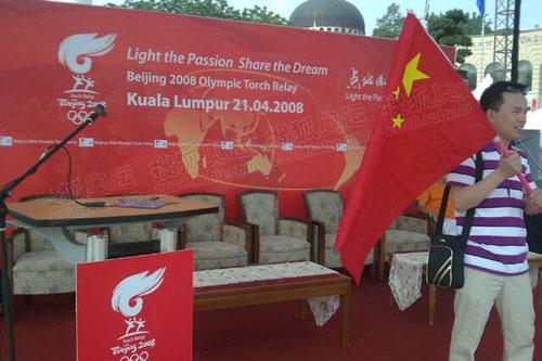 华人举旗在现场准备观看仪式