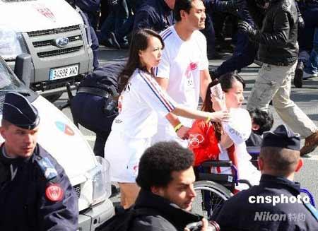 """这是4月7日拍摄的奥运火炬手金晶在北京奥运会火炬接力巴黎站的传递活动中奋力保护火炬。金晶,这位被网友们称为""""轮椅上的微笑天使""""、""""最美丽的火炬手""""的27岁女孩,是来自上海的残疾人击剑运动员。北京时间4月7号下午6点30分,奥运圣火在巴黎传递,少数藏独分子企图抢夺火炬破坏传递活动,竟然把黑手伸向了坐在轮椅上的火炬手金晶。面对突如其来的冲击,柔弱的金晶紧紧抱着火炬,凶狠的暴徒拉扯着她的胳膊,她扭过身让出后背,用整个身体来保护火炬,最终暴徒被警察制服并带走。(本组图片为我社特约播发)中新社发贾婷 摄"""