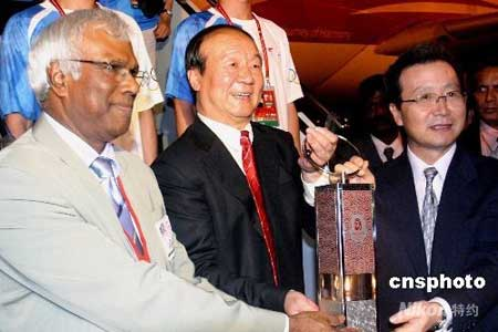 """4月20日凌晨2时12分,载有北京奥运圣火的""""奥运圣火号""""飞抵马来西亚首都吉隆坡。吉隆坡是北京奥运圣火传递""""和谐之旅""""的第十三站。图为北京奥组委执行副主席蒋效愚(中)与马来西亚奥运理事会副主席苏立(左)及中国驻马来西亚大使程永华(右)共举圣火灯。中新社发沈晨 摄"""