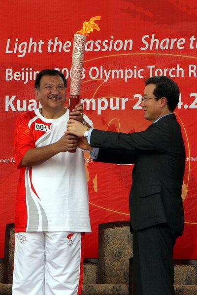 中国驻马来西亚大使程永华将火炬移交给马来西亚奥运理事会主席东姑伊姆拉
