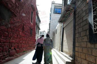 图为拉萨生活的人们和洒满阳光的街道。