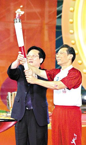 张广宁与钟南山共同握住火炬,点燃舞台前沿火炬台,亚运圣火熊熊燃起。