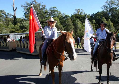 黄金海岸的天堂农庄,澳洲牛仔撑开五星红旗,骑马引领中国旅客进入景区。(中新社,任晨鸣摄。)