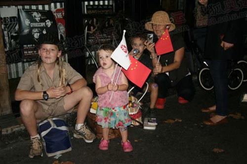 悉尼市中心街道,两个小朋友在家长陪同下,手持中国国旗与北京奥运旗玩耍。