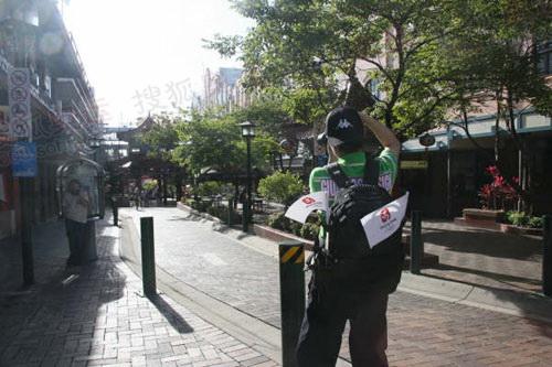 布里斯班,一名来自中国的游客在拍中国城,他身背两面北京奥运小旗。