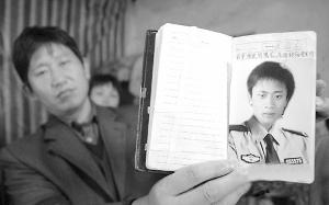 老潘(左)打开儿子生前的笔记本让人看他儿子的照片