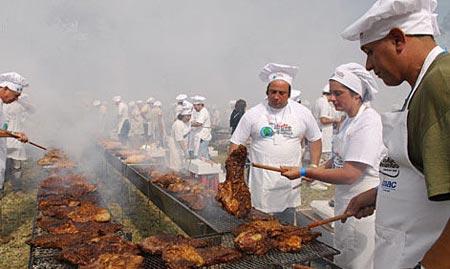"""4月13日,厨师们在乌拉圭蒙得维的亚举行的""""世界上最大规模的烧烤""""活动上忙碌。"""