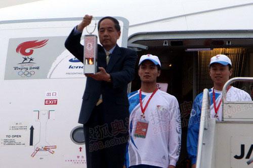4月25日,北京奥组委执行副主席李炳华手持火种灯走出机舱。当日,北京奥运圣火抵达日本东京。(摄影:李威)