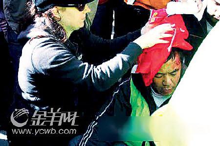救护人员正在为受伤的华裔男子做治疗。