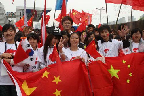 今天现场的气氛非常热烈,尽管现在现场下着小雨,但是仍然有接近3000名华人华侨留学生到现场为北京奥运会圣火加油助威。