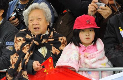 寒风中,老奶奶和小女孩披上了薄毯和外套