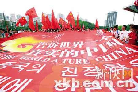 """■200余名中国留学生打出了一幅写有""""告诉世界一个真实的中国""""的巨型横幅迎接圣火传递。新华社发"""
