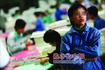 """东莞沙田一家泡沫厂,穿着工服的童工。他们被工头从家乡拐来,以低廉的价格""""卖""""给工厂。本报记者方光明摄"""