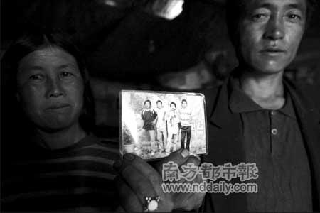 马海曲布的父母拿着儿子的照片。