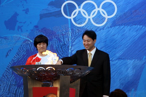 1988年奥运会开幕式上表演滚铁环的时年只有6岁的小男孩尹泰雄今天担任最后一棒火炬手与首尔市市长吴世勋一同点燃圣火盆01