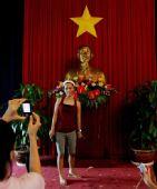 图文:一名游客在统一宫内的胡志明塑像前留影