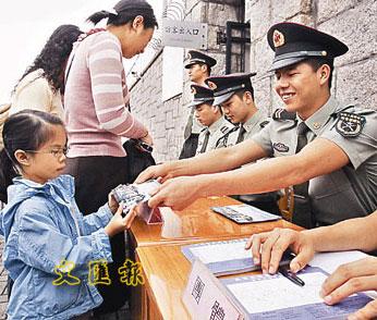 一名小朋友27日从解放军叔叔手中领取门票后,非常高兴。(图片来源:文汇报)
