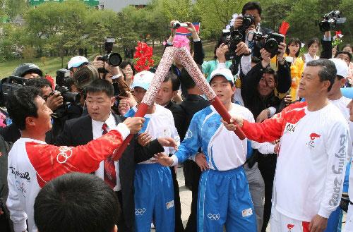 4月28日,中国驻朝鲜大使刘晓明(右)与朝鲜火炬手交接。当日,北京奥运会圣火传递活动在朝鲜平壤举行。这是北京奥运会圣火境外传递的第十八站。 新华社记者高浩荣摄
