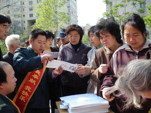 """志愿者在社区指导居民填写""""微笑传递卡"""""""