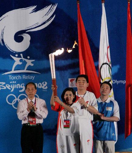 4月29日,奥运火炬手阮氏秋霞(左二)在起跑仪式上展示点燃的火炬。当日,北京奥运圣火传递活动在越南胡志明市举行。  新华社记者周磊摄