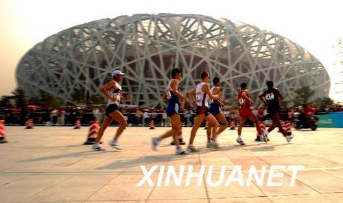 """4月18日,运动员从""""鸟巢""""前经过。当日,""""好运北京""""国际田联竞走挑战赛男子20公里比赛在国家体育场――""""鸟巢""""举行。新华社记者李尕摄"""
